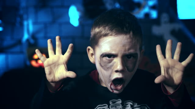 Scary-little-boy-wearing-skull-makeup-for-Halloween-using-fingers-to-scare