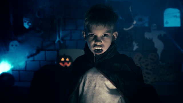 Young-boy-in-a-vampire-costume-for-Halloween-showing-his-scary-face-and-teeth-to-camera