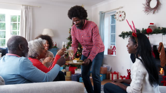 Man-Serving-Champagne-And-Snacks-As-Adult-Members-Of-Family-Celebrate-Christmas-At-Home