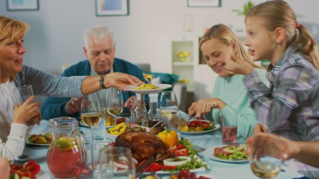 Gran-familia-y-fiesta-de-amigos-en-casa-grupo-diverso-de-personas-jóvenes-y-adultos-se-reunieron-en-la-mesa-Comer-compartir-comidas-beber-y-divertirse-Fiesta-durante-el-día-