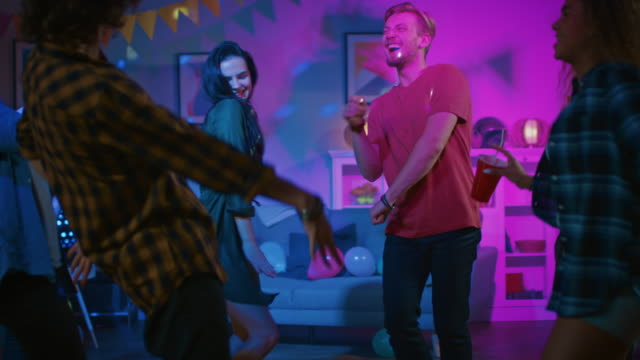 At-the-College-House-Party:-Diverse-Group-of-Friends-Have-Fun-Dancing-and-Socializing-Boys-and-Girls-Dance-in-the-Circle-Girl-Takes-Glass-with-Drink-from-the-Tray-and-Joins-the-Group-