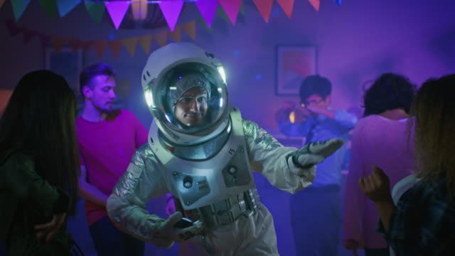 At-the-College-House-Costume-Party:-Fun-Guy-Wearing-Space-Suit-Dances-Off-Doing-Groovy-Funky-Robot-Dance-Modern-Moves-With-Him-Beautiful-Girls-and-Boys-Dancing-in-Neon-Lights-In-Slow-Motion-