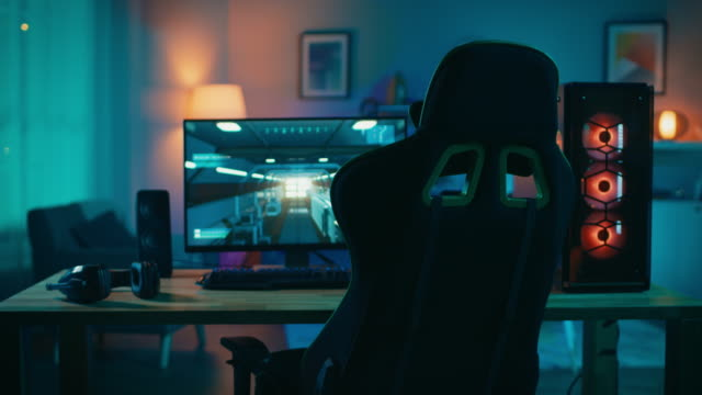 Powerful-Personal-Computer-Gamer-Rig-with-First-Person-Shooter-Game-Paused-on-Screen-Monitor-Stands-on-the-Table-at-Home-Cozy-Room-with-Modern-Design-is-Lit-with-Warm-and-Neon-Light-