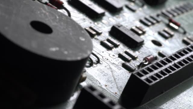 Rotación-de-circuitos-de-computadora-Girando-la-placa-de-circuito-impreso-\nmicroprocesadores-condensadores-y-conectores-de-audio-parcialmente-cubierto-con-polvo-electrostático