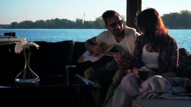 Couple-talking-while-man-is-holding-guitar-by-the-river