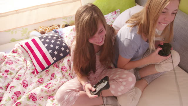 Girls-on-a-bed-playing-computer-games-in-their-pyjamas