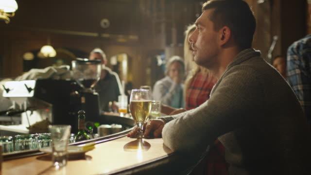 Lapso-de-tiempo-vídeos-de-un-hombre-sentado-sola-con-una-cerveza-en-el-bar-mientras-las-personas-se-encuentran-con-un-buen-momento-