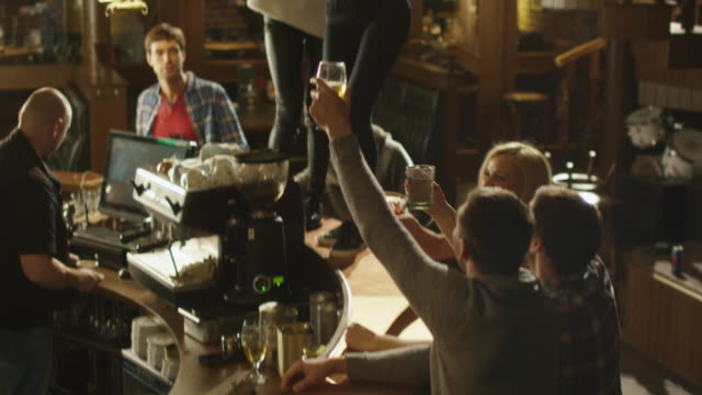 Two-girls-are-dancing-with-drinks-on-a-table-while-everybody-are-having-a-good-time-together-at-a-bar-