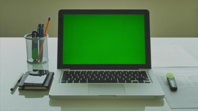 Laptop-mit-grünen-Bildschirm-auf-moderne-Glas-Tisch-im-Büro-4-K