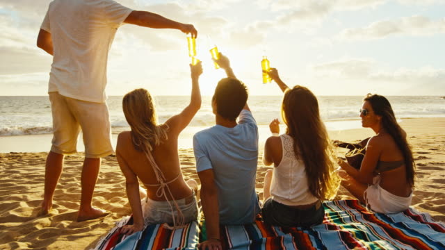 Friends-Relaxing-on-the-Beach-at-Sunset