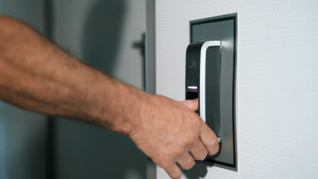 The-man-puts-his-finger-on-a-fingerprint-scanner-which-is-designed-to-enter-the-door-Modern-security-technology-in-everyday-lives-of-employees-Work-of-protection-against-burglary-close-up