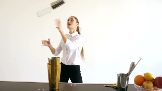 Professinal-bartender-girl-juggling-bottles-and-shaking-cocktail-at-mobile-bar-table-on-white-background-studio-indoors