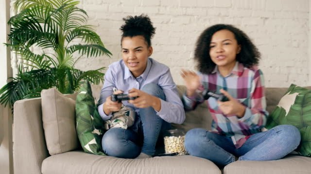 Two-mixed-race-curly-girl-friends-sitting-on-couch-play-console-computer-games-with-gamepad-and-have-fun-at-home