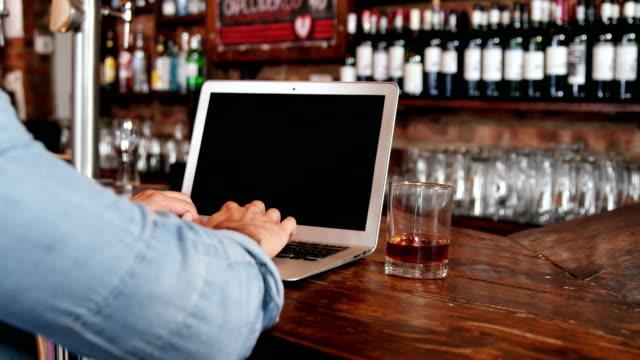 Mann-mit-Laptop-beim-Whisky-bei-Zähler