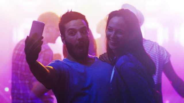 Young-Man-and-Woman-dancing-Together-Doing-Selfie-in-Nightclub-