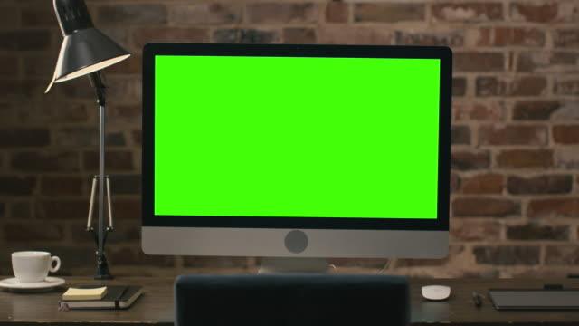 Metraje-de-un-monitor-de-computadora-con-pantalla-verde-de-pie-sobre-una-mesa-junto-a-una-tableta-lámpara-taza-de-café-cuaderno-y-ratón-en-un-altillo-