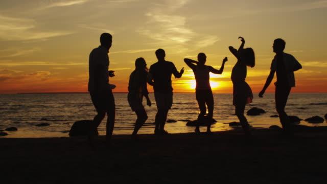 Grupo-de-jóvenes-felices-están-bailando-en-la-playa-en-Sunset-Light