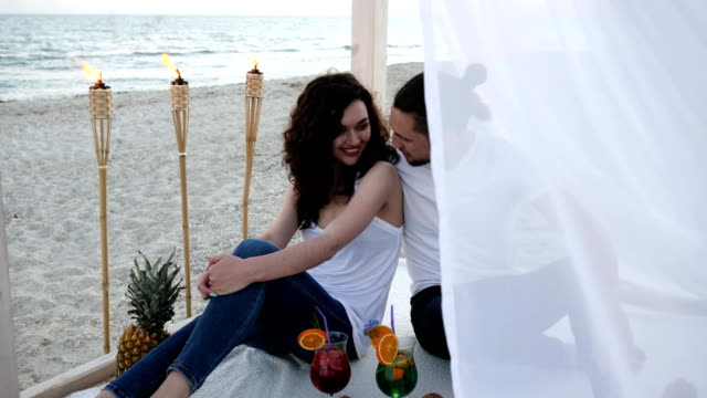 happy-couple-with-cocktails-have-fun-bungalow-with-white-cloth-an-exotic-vacation-on-background-tropical-fruits-burning-torches