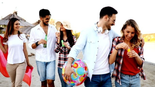 Group-of-happy-friends-partying-on-beach