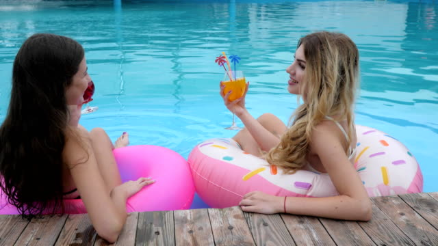Summer-vacation-Friends-on-inflatables-rings-resting-in-Poolside-Long-haired-girls-in-bathing-suits-relax-in-pool
