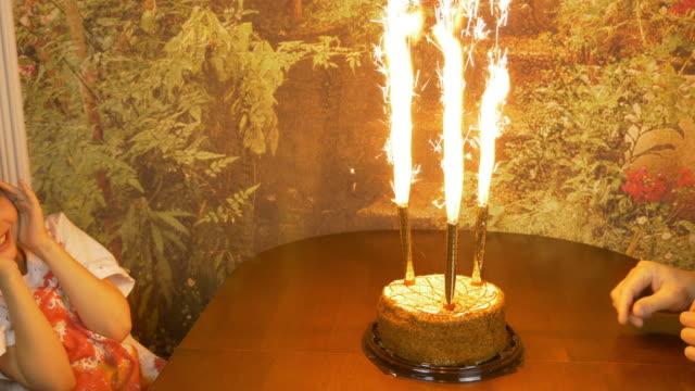 Movimiento-rápido-Muchacha-de-Palmas-de-las-manos-Sesión-chica-de-fuego-Fuentes-de-fuego-chispeante-en-un-pastel-Cumpleaños-de-las-niñas-Torta-con-luces-Chica-es-estar-mirando-la-tarta-y-con-miedo-