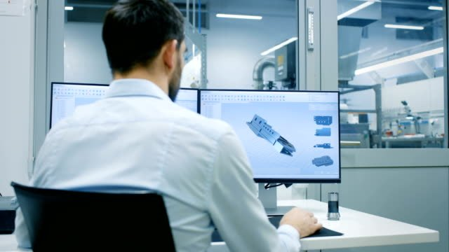 Engineer/-Technician-Working-on-a-Personal-Computer-with-Two-Displays-He-s-Designing-New-Component-in-CAD-Program-Out-of-the-Office-Window-Components-Manufacturing-Factory-is-Seen-
