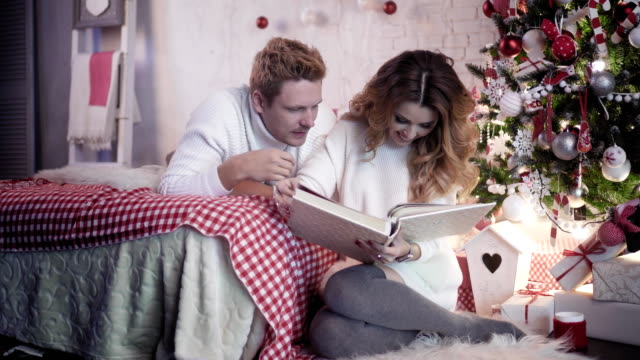 Young-beautiful-looking-at-photo-album-on-bed-near-christmas-tree
