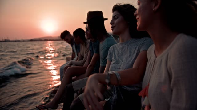 Young-multi-ethnic-hipster-friends-on-summer-holidays-sitting-on-jetty