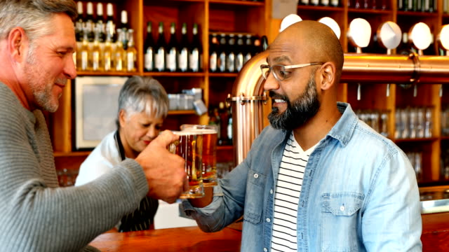 Friends-toasting-glass-of-beer-at-counter-in-restaurant-4k