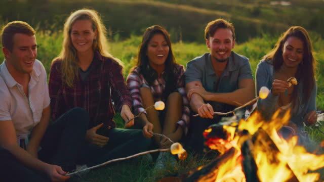 Freunden-entspannen-bei-Sonnenuntergang-am-Lagerfeuer