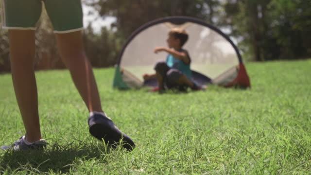 Niños-felices-en-el-campamento-de-verano-jugando-fútbol-coinciden-en-los-niños-de-campo-de-pasto-verde-patadas-pena-portero-lenta