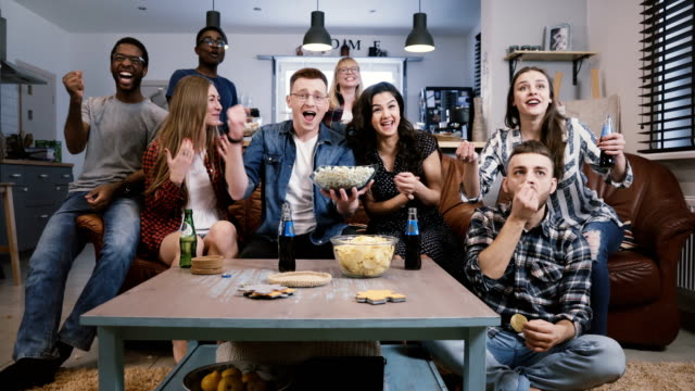 Friends-watch-sports-on-TV-cheer-and-celebrate-Happy-diverse-supporters-fans-sit-on-couch-with-popcorn-and-drinks-4K
