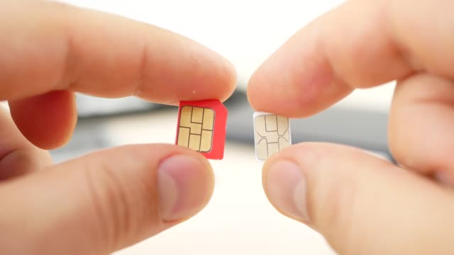 Hand-holding-a-red-micro-SIM-and-white-nano-SIM-cards