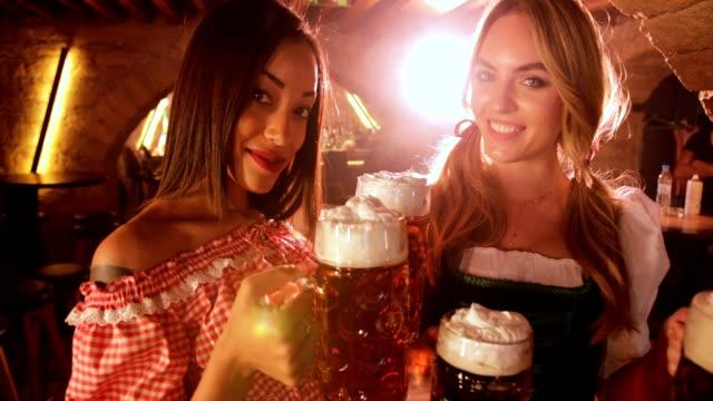 Beautiful-multi-ethnic-women-holding-beer-mugs-at-Oktoberfest-festival-celebration