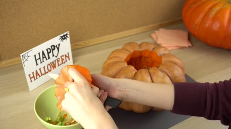 Women-s-hands-clean-the-pumpkin-cover-from-the-seeds-for-halloween