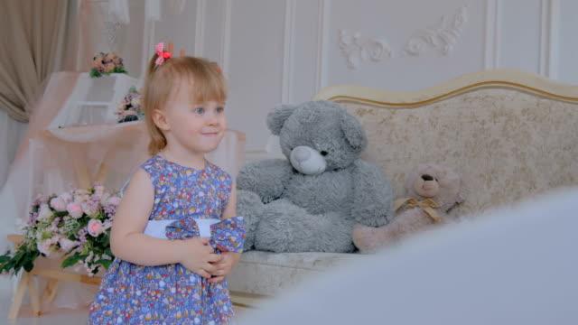 Retrato-de-divertida-niña-con-muñeca-de-oso-en-casa