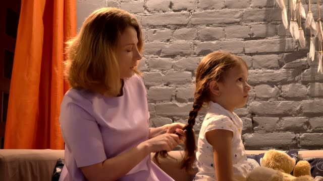 Mother-braiding-her-little-daughter-s-hair-parent-and-kid-sitting-together-on-sofa-family-concept-indoors