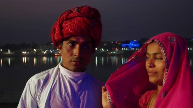 Portrait-of-an-Indian-couple-against-the-background-of-lights-reflecting-on-the-holy-lake-of-Pushkar-Rajasthan