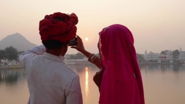 Pan-left-to-couple-in-Indian-dress-taking-photos-of-sunset-at-a-holy-lake-in-Rajasthan