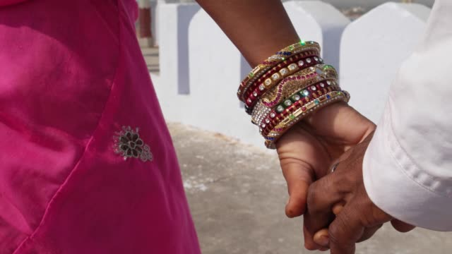 Close-up-of-a-couple-s-hands-with-bangles-and-traditional-Indian-clothes