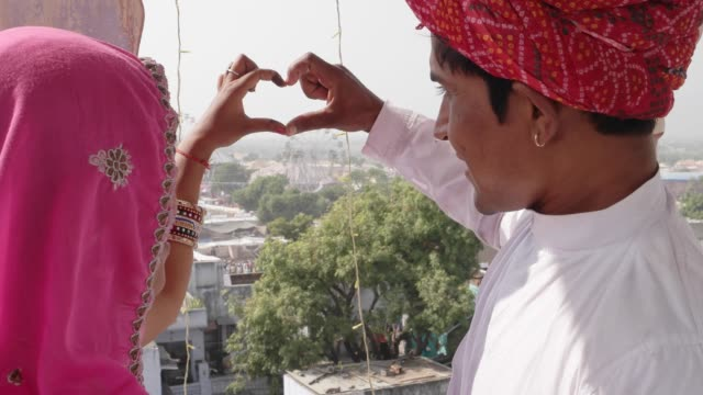 Indian-couple-in-traditional-dress-make-heart-symbol-with-fingers-and-hand-looking-down-from-a-vantage-point-at-Pushkar-Mela-festival-in-Rajasthan-India