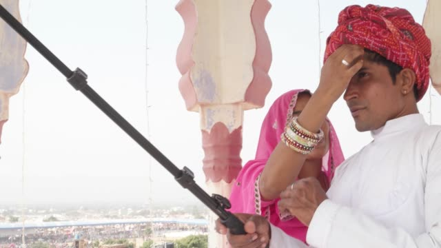 Attractive-Indian-couple-in-traditional-dress-getting-ready-and-take-selfies-on-their-mobile-phone-camera-in-Rajasthan-India