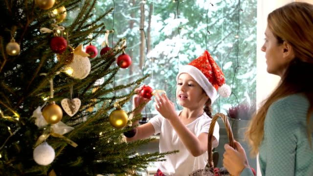 Little-cute-girl-with-her-mom-decorate-the-Christmas-tree