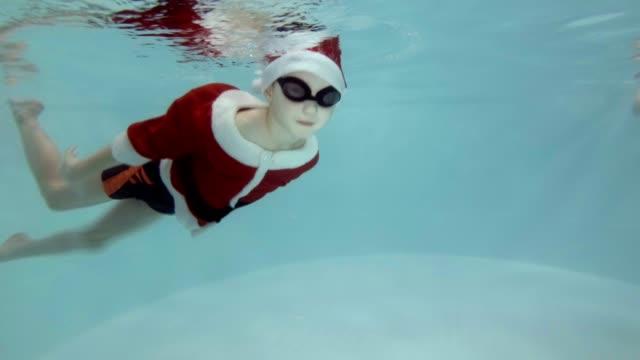 Un-niño-vestido-de-Santa-Claus-va-deportes-con-un-entrenador-en-la-piscina-Nada-bajo-el-agua-a-las-escaleras-en-gafas-de-natación-y-mira-a-la-cámara-