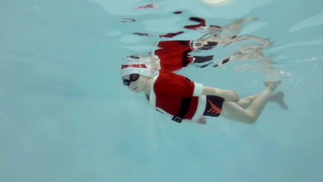 Un-niño-con-traje-y-sombrero-de-Santa-Claus-nada-bajo-el-agua-en-la-piscina-con-gafas-para-natación-y-mirando-a-la-cámara-Cámara-lenta-Vista-lateral-Video-de-RAW-Tiro-bajo-el-agua-