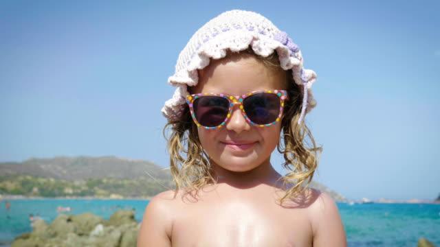 Retrato-de-hermosa-niña-divirtiéndose-en-el-mar-lindo-sonriendo-en-Panamá-crema-de-protección-solar-Fondo-de-agua-de-mar-azul-y-rocas-