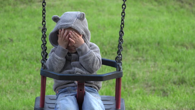 Funny-child-playing-hide-and-seek-smiling-boy-balancing-in-a-swing-chair