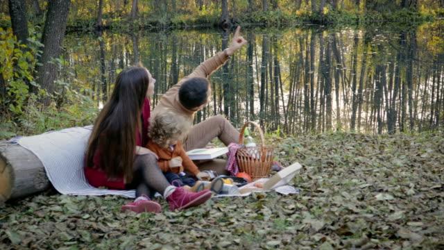 Familia-feliz-en-picnic-cerca-del-lago-en-el-bosque