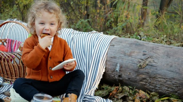 Cute-curly-haired-toddler-eating-cookies-and-watching-the-phone-in-the-park-on-a-picnic
