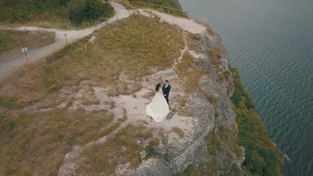 Young-and-beautiful-wedding-couple-together-on-the-slope-of-the-mountain-near-sea-Lovely-groom-and-bride-Shooting-from-the-air-Aerial-shot